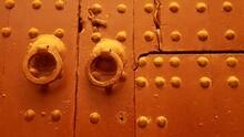 Old Wooden Studded Double Doors In Golden Brown Paint In Marrakesh Morocco, With Original Antique Door Knobs And Key Holes
