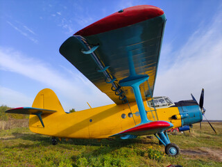Yellow and blue old biplane plane with a single piston engine and propeller against a blue sky with clouds on the airfield with green grass in summer