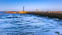 Early Evening View Of Harbour Pier Walls With Various Lighthouses And Beacons Against A Blue Sky And White Crested Waves In The Foreground.