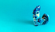 A Ceramic Rooster In The So-called Gzhel (Gzhel Is A Russian Style Of Blue And White Ceramics) On A Blue Background.
