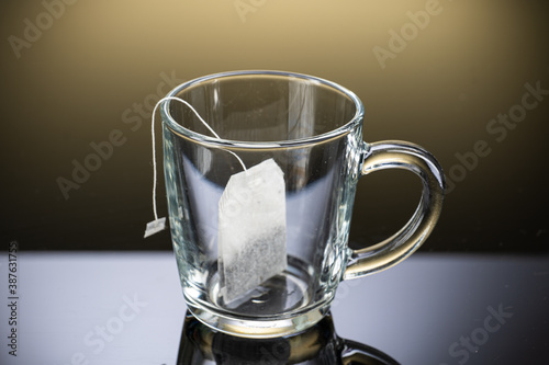 Brew black tea from a sausage bag in a transparent mug with reflection on a grad Fotobehang