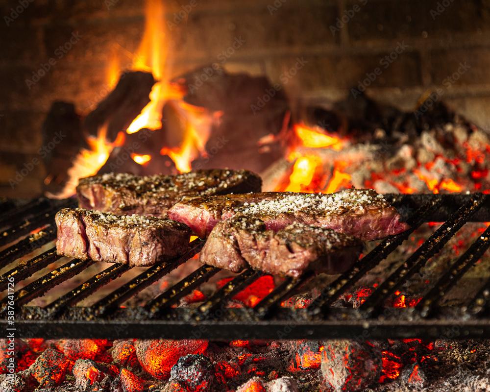 Fototapeta Vista de frente de 4 pedazos de carne, asado al carbon y leña, parrilla de metal y colores calientes