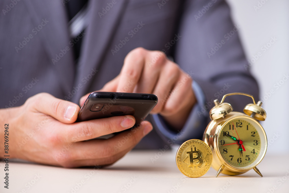 Fototapeta Young man earning money via Internet in time management concept