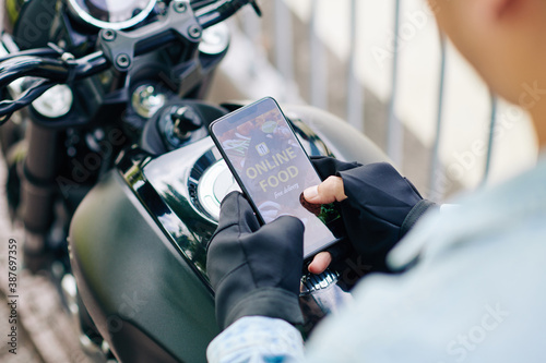 Fototapeta Close-up image of motorcyclist ordering food via mobile application obraz