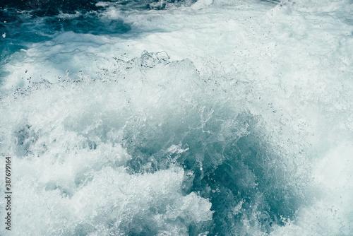 Fototapeta Frozen splashing in rapids of powerful mountain river