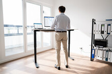 Man Working On Computer At Standing Desk