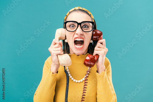 Woman holding two telephone receivers and shouting