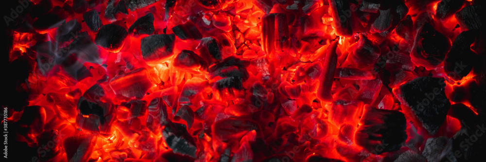 Fototapeta hot red coals among black ash, wallpapers for mobile devices, abstract
