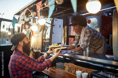 Obraz caucasian beardy hipster taking two sandwiches from polite female afro-american employee in fast food service - fototapety do salonu