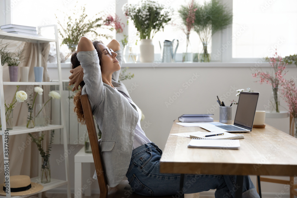 Fototapeta Calm young Caucasian female designer sit lean relax in chair in own atelier or office, relieve negative emotions. Relaxed woman florist rest at workplace, take break from work. Stress free concept.