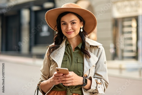 Obraz Portrait of a young beautiful stylish woman wearing autumn coat and hat holding her smartphone, looking at camera and smiling while standing on city street - fototapety do salonu