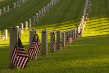 Row Of Veterans Headstones Decorated With American Flags For Memorial Day Remembrance