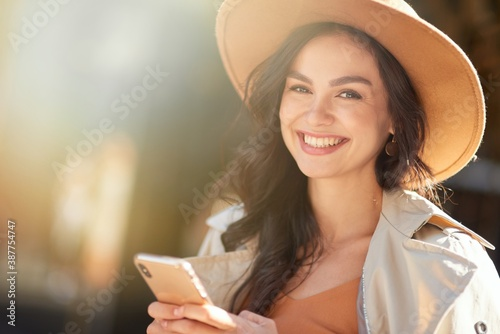 Obraz Portrait of a young beautiful and happy caucasian woman wearing hat using smartphone and smiling at camera while standing on the city street on a sunny day - fototapety do salonu