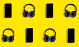 Black headphones and mobile phone on a yellow background. Concept of musical streaming.