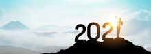 Silhouette Of Businessman Show Hand Up With Happy New Year 2021 On Top Of Mountain.