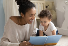 Happy Young Biracial Mom And Little Ethnic Toddler Child Sit On Floor In Children Room At Home Reading Book Together. Smiling Loving African American Mother Have Fun Play Study With Small Infant Baby.