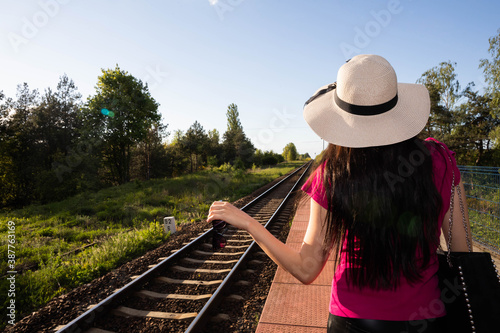 A woman in a hat is standing on a railway platform and awaits the arrival of a train that will take it to look for her dream adventure Canvas