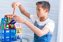 Child Plays With A Magnetic Constructor On Glass Table. Boy Building A Toy House From Blocks. Kid Playing With Colorful Toy Blocks.