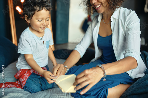 Indoor image of cheerful excited little boy sitting on bed with his young mom making toy plane, folding paper Wallpaper Mural