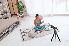 Young Woman Using DSLR Camera For Live Streaming Teach Yoga Online In Living Room.