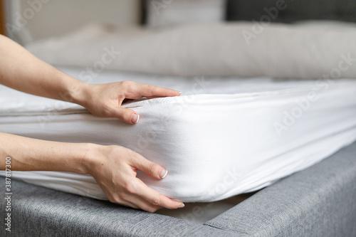 Woman putting new orthopedic mattress on sleeping bed Canvas Print