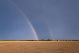 Fototapeta Tęcza - Dwie tęcze na tle bużowego nieba i zoranego pola.