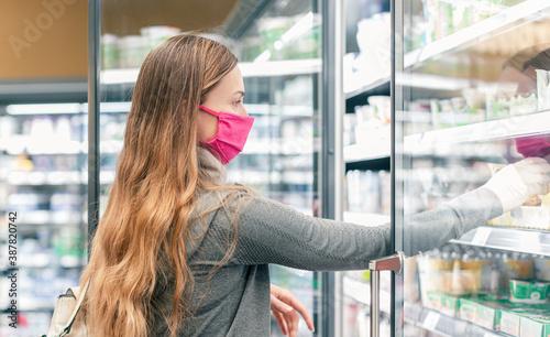 Fotografia, Obraz Woman in supermarket shopping in dairy isle during lockdown