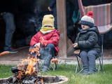 Two caucasian little boys grilling sausages on sticks on open fire in the autumn garden.