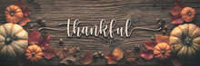 """Thankful"" Message On Rustic Harvest Table Background Decorated With Pumpkins Acorns And Leaves"