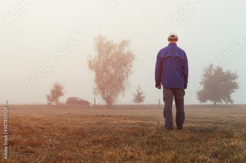 Young man walking in misty autumn morning fog to parking car at sunrise Fotobehang
