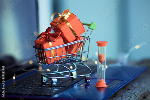 Fotografie, Obraz Hourglass and small basket  with boxes of Christmas gifts on the background of a laptop