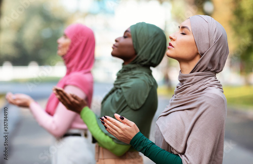 Obraz Three Muslim Women Praying Together Standing Outdoors Wearing Traditional Hijab - fototapety do salonu