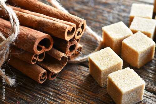 Photo A close up image of fresh cinnamon sticks and brown sugar cubes.