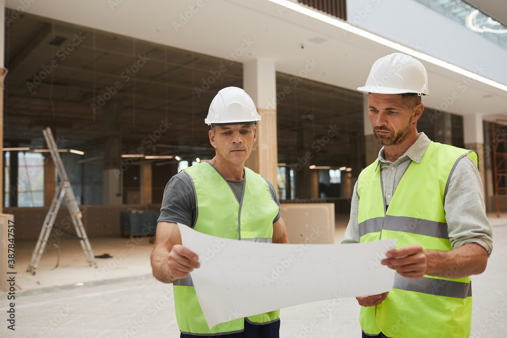 Fototapeta Waist up portrait of two professional building contractors looking at plans while standing at construction site, copy space