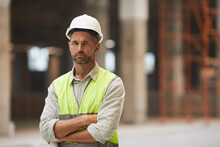 Waist Up Portrait Of Mature Construction Worker Looking At Camera While Standing With Arms Crossed At Construction Site, Copy Space