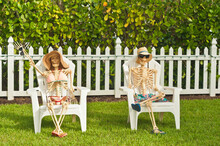 Front View, Medium Distance Of Two Skeletons Sitting On Lawn Chaired As A Halloween Display At A Tropical Residence On Coast Of Gulf Of Mexico, On Sunny Day