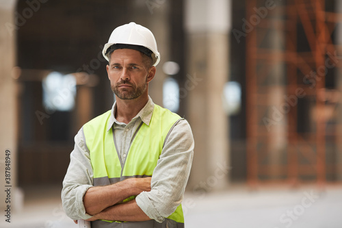 Obraz Waist up portrait of mature construction worker looking at camera while standing with arms crossed at construction site, copy space - fototapety do salonu