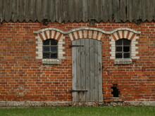 Facade Of A Brick Built Old Outbuilding With Wooden Door And Small Windows