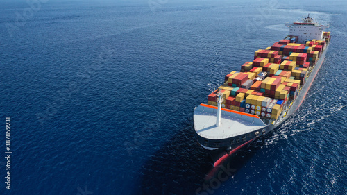 Fototapeta Aerial drone photo of huge container tanker ship carrying truck size colourful c