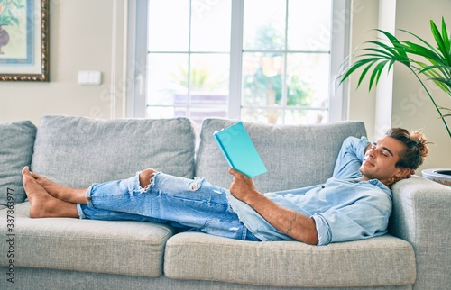 Obraz na plátně Young hispanic man smiling happy reading book laying on the sofa at home
