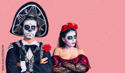 Young couple wearing mexican day of the dead costume over background skeptic and nervous, disapproving expression on face with crossed arms Billede på lærred