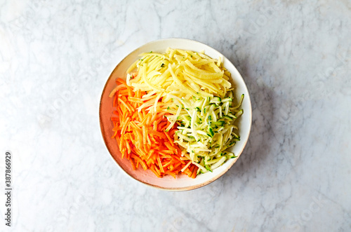 Valokuvatapetti Grated potatoes, zucchini and carrots for healthy fritters