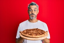 Middle Age Grey-haired Man Holding Italian Pizza Puffing Cheeks With Funny Face. Mouth Inflated With Air, Catching Air.