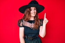 Young Beautiful Woman Wearing Witch Halloween Costume Smiling With An Idea Or Question Pointing Finger Up With Happy Face, Number One