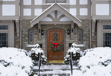 Old Fashioned Tudor Style House With Christmas Wreath On Front Door And Snow Covered Bushes