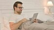 Online Video Chat on Tablet by Young Man in Bed