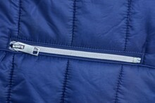 One White Closed Metal Zip On The Pocket On A Blue Synthetic Fabric