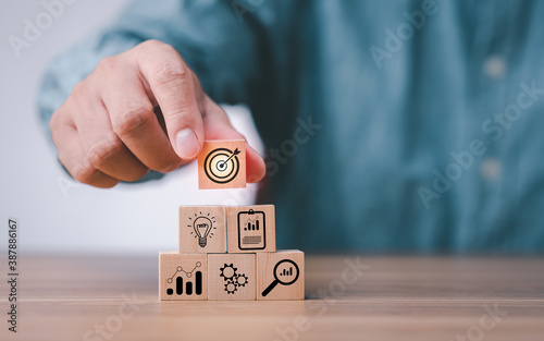 Fototapeta idea of goal and target. hand stack woods block step on table with icon business strategy and Action plan. business development concept.copy space. obraz