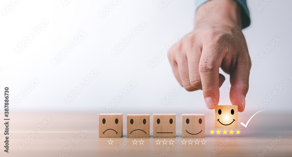 Fototapeta best excellent business services rating customer experience. Satisfaction survey concept. Hand of a businessman chooses a smiley face on wood block cube. 5 Star Satisfaction.