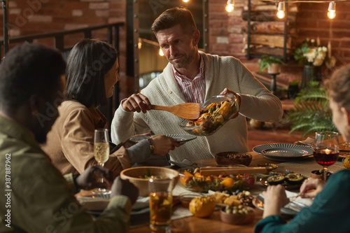 Fototapeta Portrait of handsome mature man serving food while hosting dinner party with friends and family, copy space obraz na płótnie